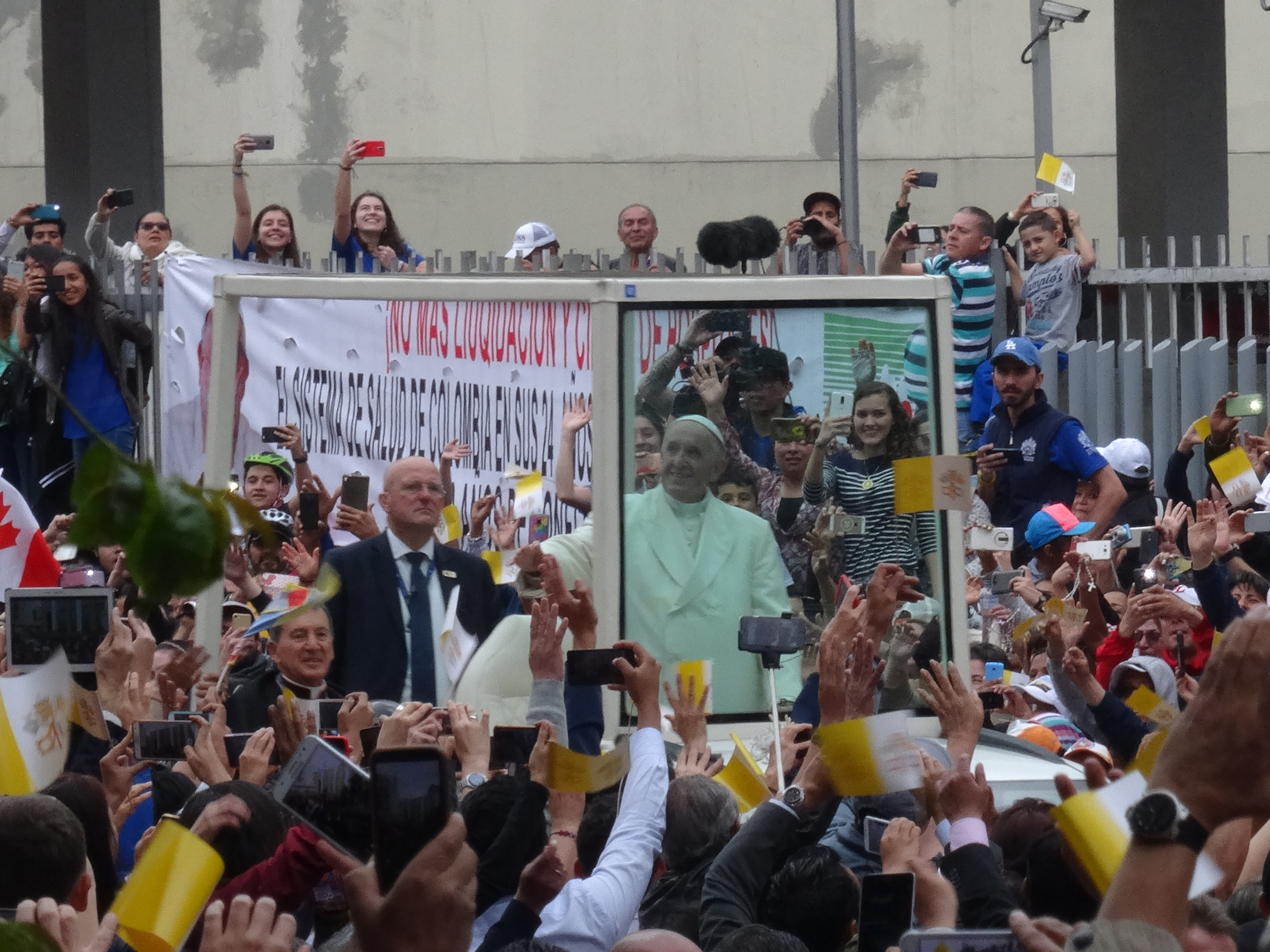 Pope in Popemobile with people surrounding him.