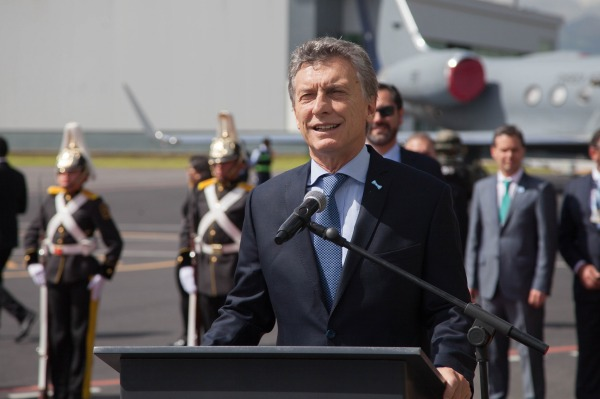 Man delivers a speech on an airfield.