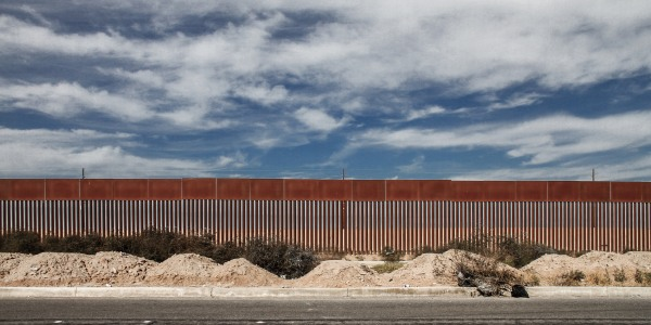 A large border fence and the blue sky as seen from a street in California