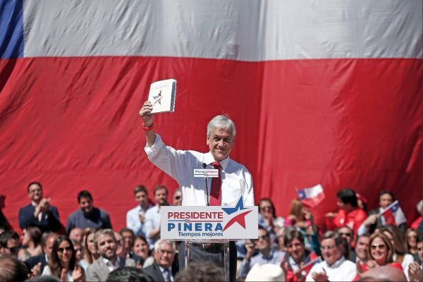 A presidential candidate stands in front of a crowd and a large Chilean flag