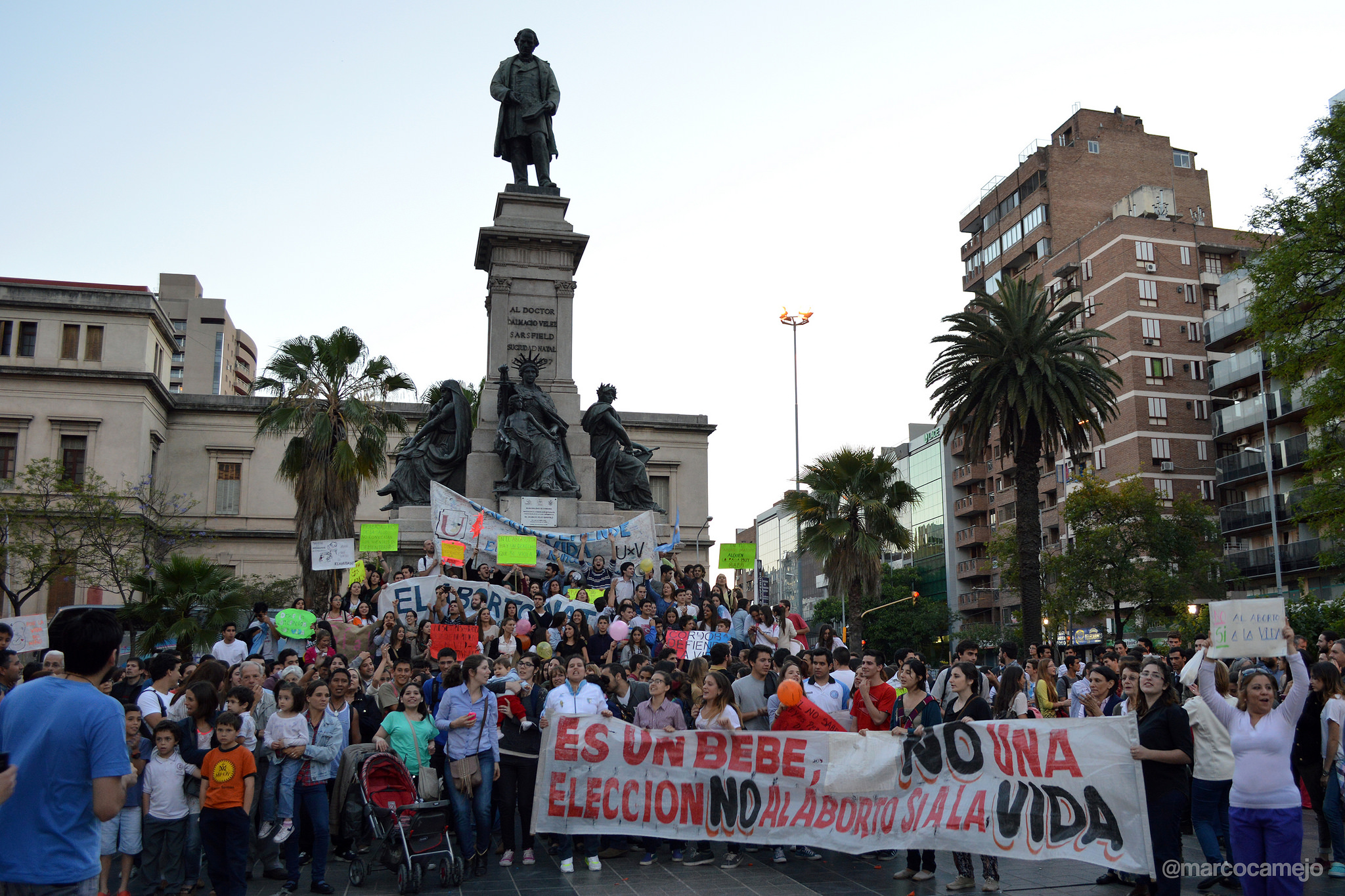 A large group of women and men gather in front of statue in a plaza.