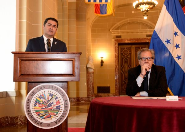 One man stands at a podium while another sits at a table