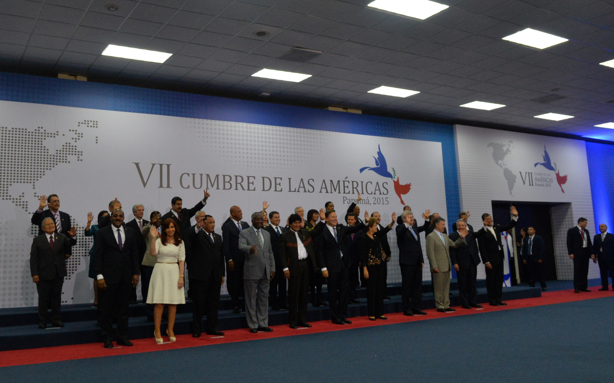 Large group of men and women stand awkwardly while waving to a crowd