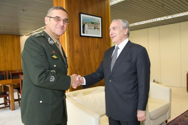 A man in a military uniform and a man in civilian dress shake hands