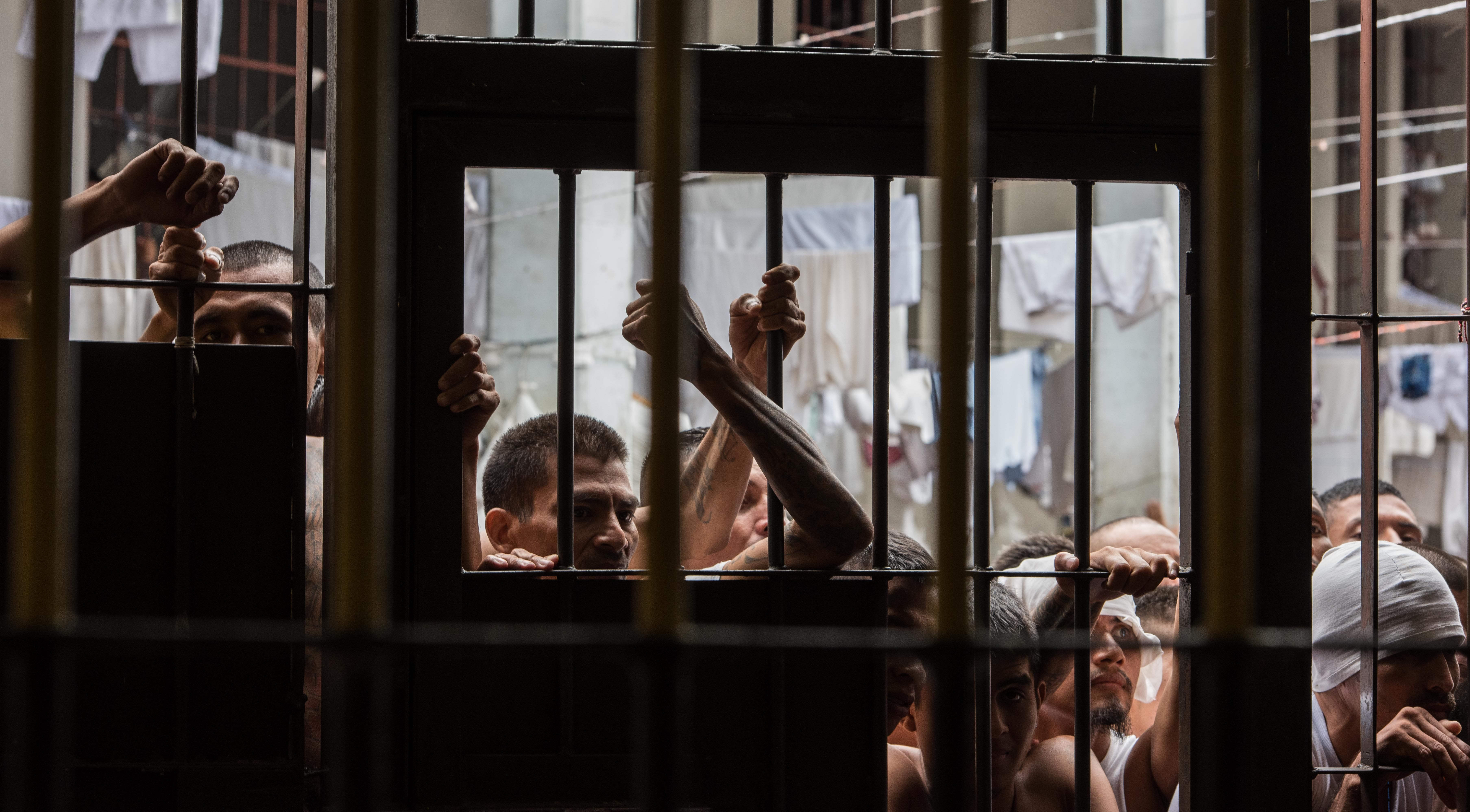 Gang members gather behind bars