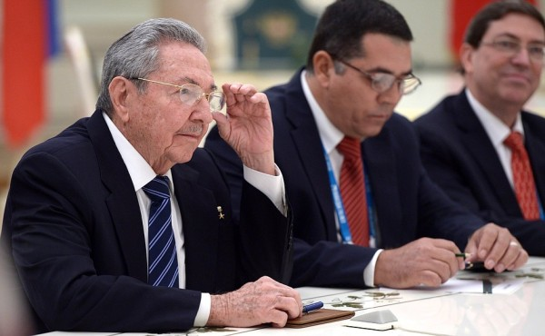 Raúl Castro sits at a table with two men.