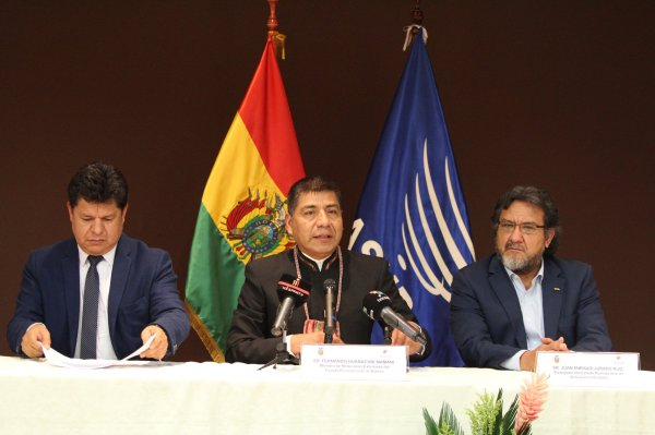 Three men sit at a table with microphones and two flags behind them.