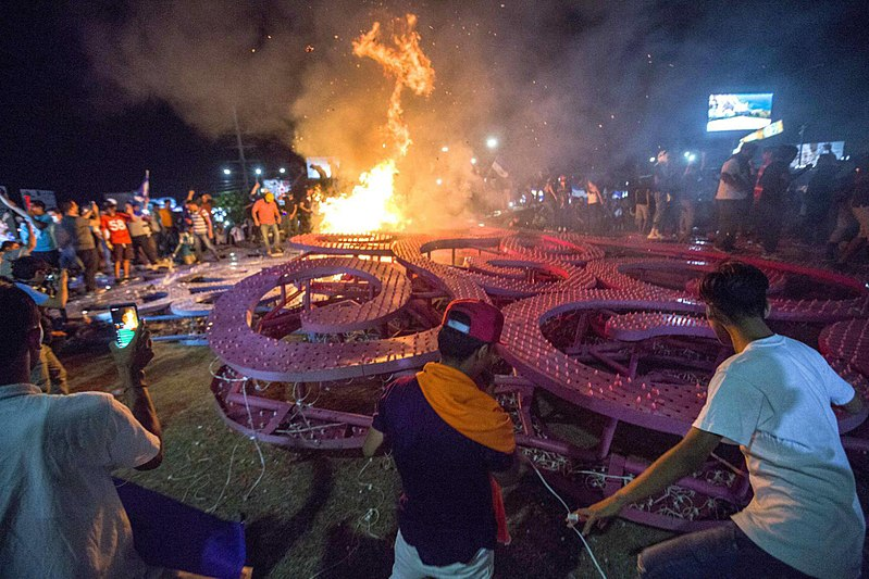 Protesters burn a large pink metal tree
