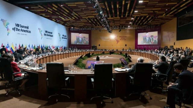 A large round table encompasses a room with various heads of state from the Americas