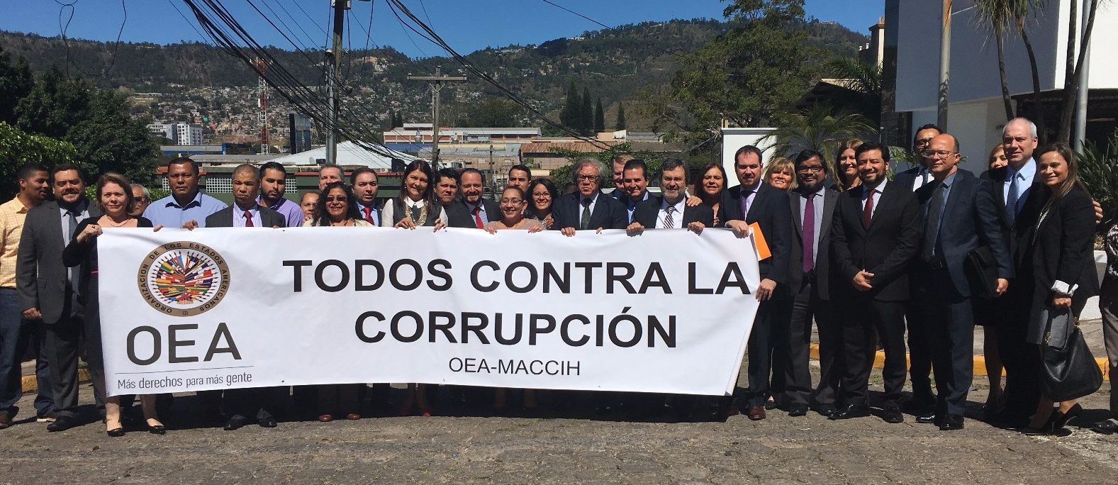 Photo of MACCIH and OAS representatives holding a banner with OAS logo