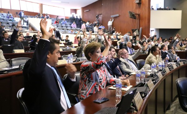 Several people raise their hands in the Honduran National Congress