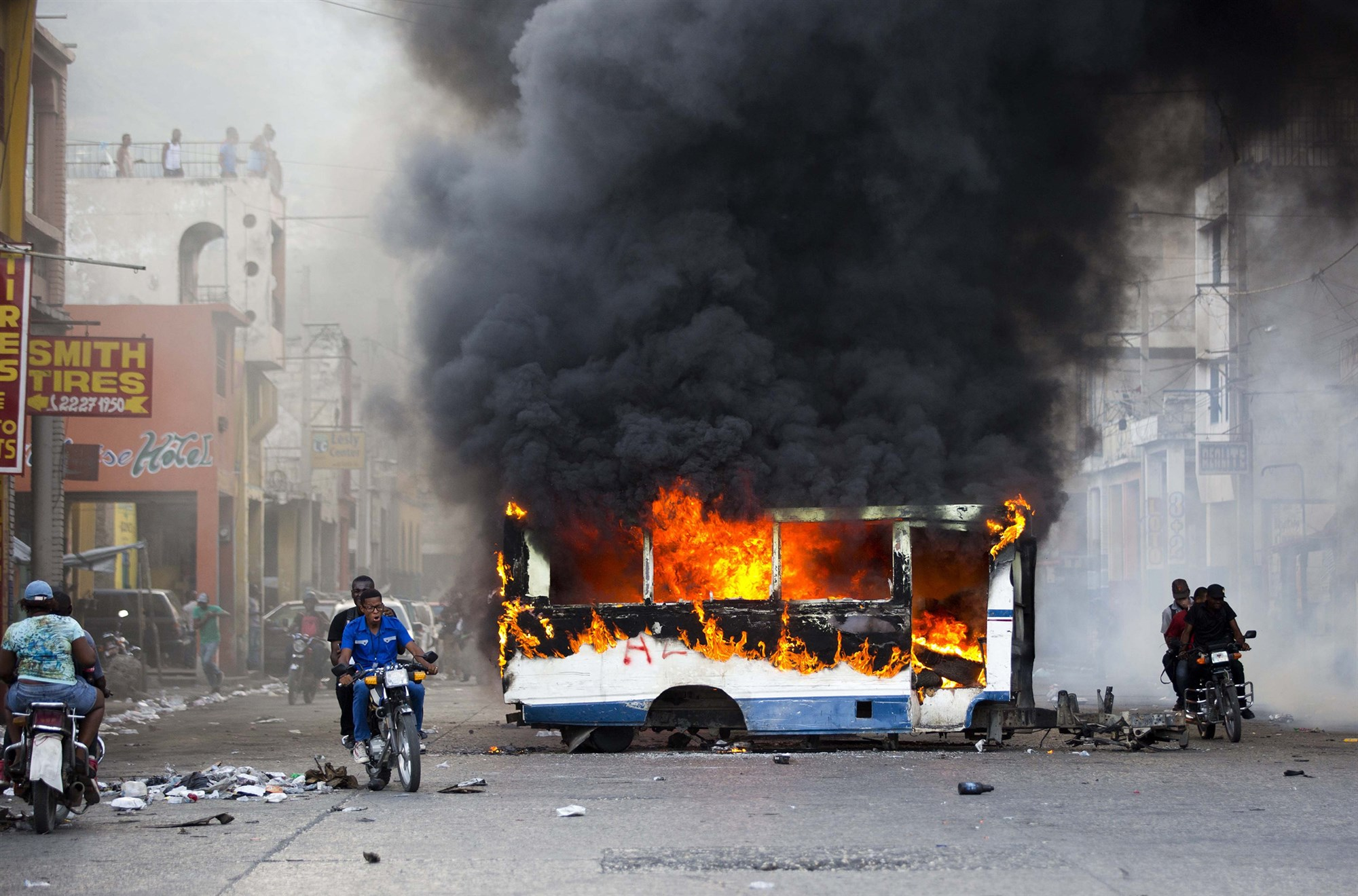 A bus burning with thick clouds of black smoke billowing above it, and two men on a motorcycle riding by.
