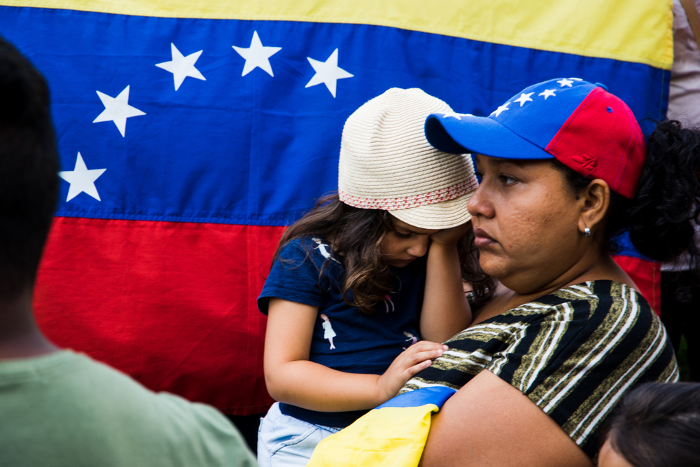 A group of Venezuelans protest against International Contact Group for Venezuela. The Venezuelan flag is held in the background as a protester holding a young child looks on.