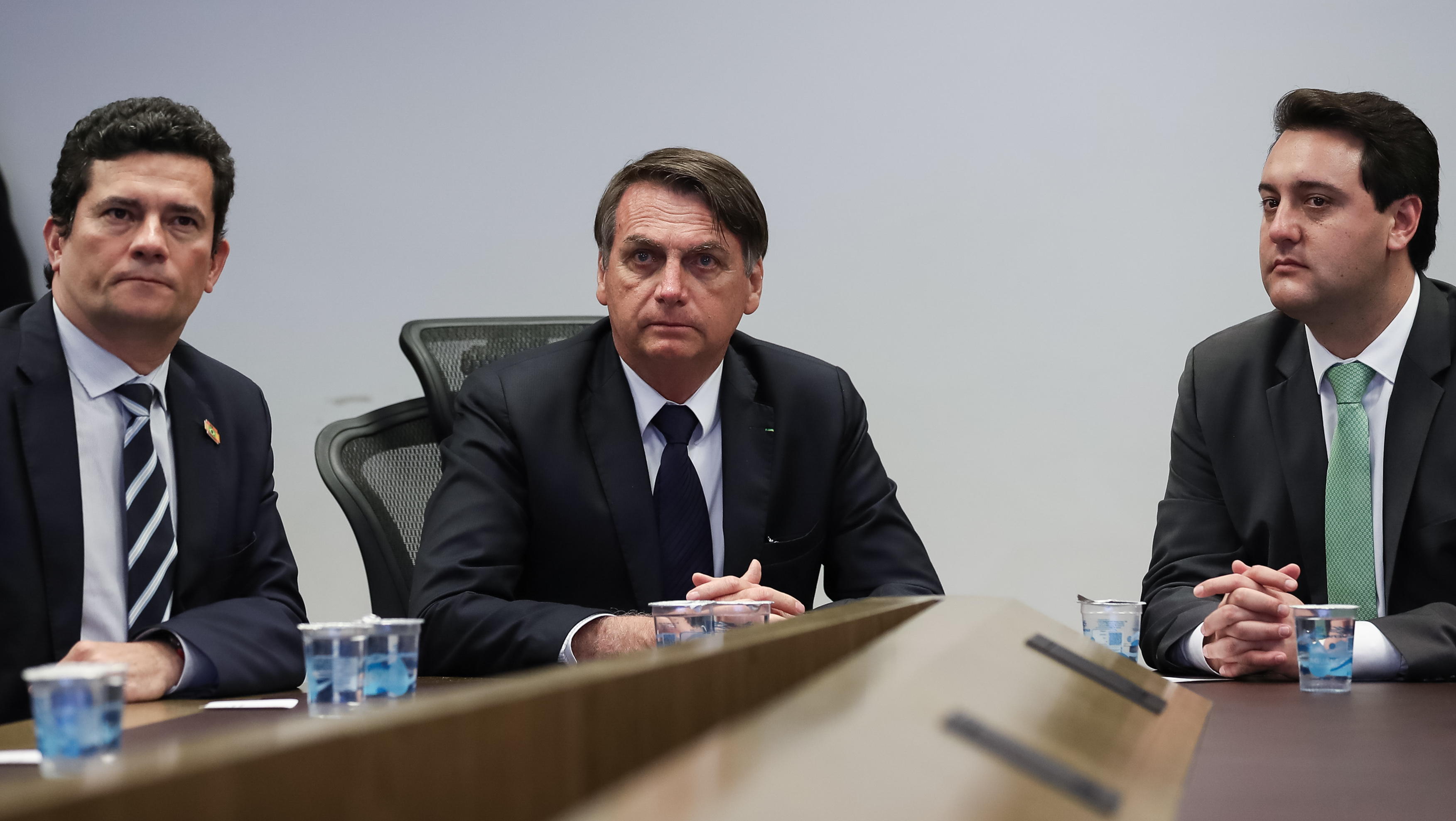 Moro, Bolsonaro, and Paraná governor Ratinho Júnior seated during a visit to the Integrated Center of Intelligence and Public Security of the Southern Region in May 2019.