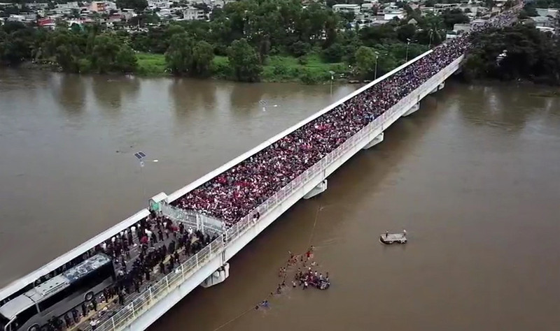 The Honduran refugee caravan crowds a bridge in October 2018