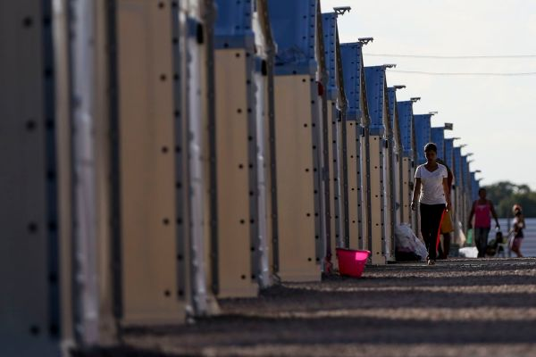 Venezuelan migrants walk past UNHCR tents at a camp in Boa Vista, Roraima