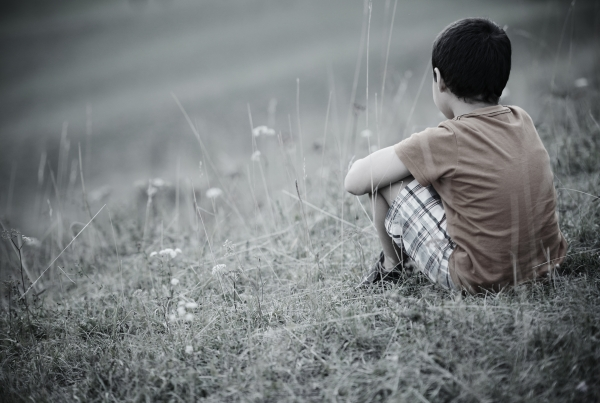 Child sitting down on a grass field
